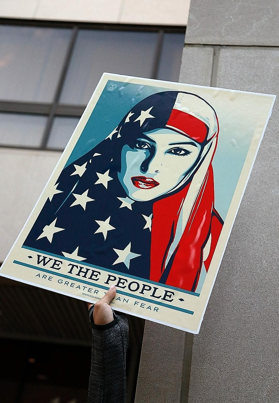 A protest sign at a Miami rally last week against Mr Trump's travel restrictions on people from seven Muslim-majority countries. Identity politics is visceral and animal-like, and once awoken, is difficult to put back into its cage, says the writer.