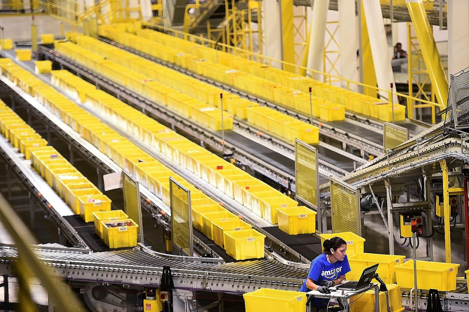 An employee auditing outgoing shipments moving along a conveyor belt at an Amazon facility in California. The firm is looking to transform the shipping industry, says Bloomberg columnist Adam Minter.