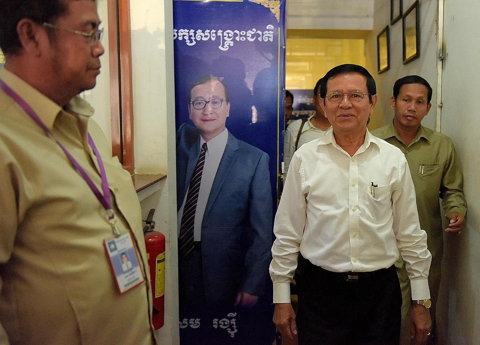 CNRP acting president Kem Sokha (in white shirt) walking past a portrait of exiled leader Sam Rainsy, who resigned as president of the opposition party recently, at its headquarters in Phnom Penh on Sunday. CNRP, Cambodia's leading opposition party,