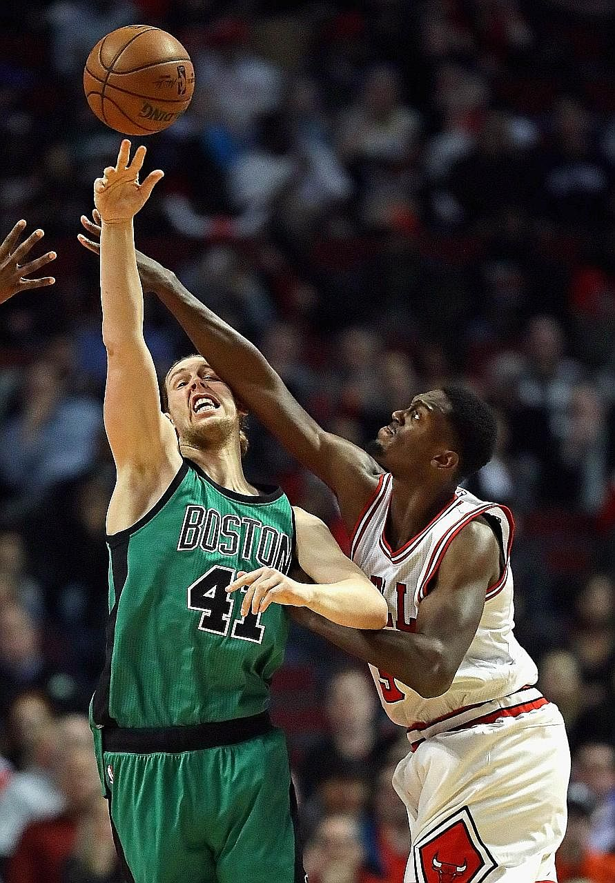Celtics centre Kelly Olynyk makes a pass under pressure from Bulls forward Bobby Portis at the United Centre. Olynyk had 17 points off the bench while Portis scored 19 of the 34 points contributed by the Bulls' reserves.