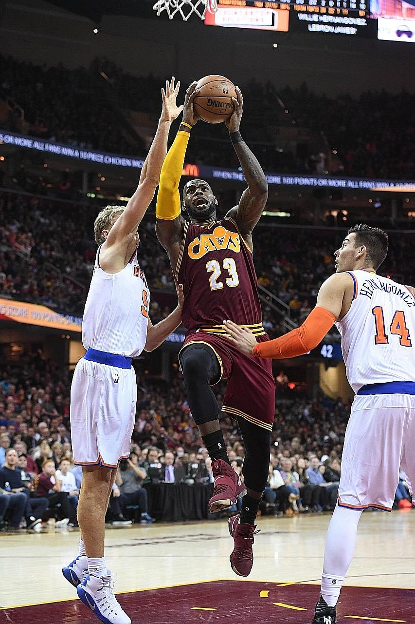 LeBron James shoots between Mindaugas Kuzminskas (left) and Willy Hernangomez of the New York Knicks. Despite a 119-104 win, the Cavaliers were chastised for a lacklustre period in the third quarter.