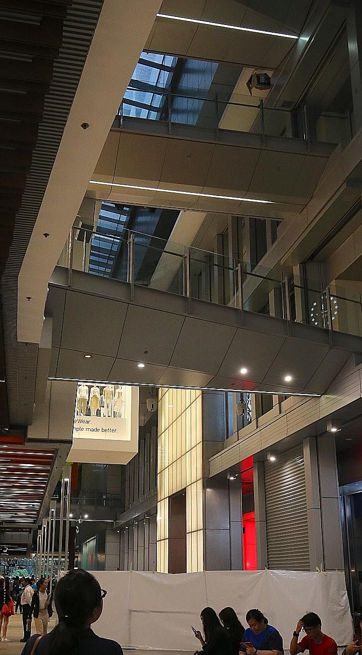 """The teenager was said to be taking a photo on the fourth-storey linkway (right) between Orchard Central and Orchard Gateway yesterday afternoon when his phone fell onto a ledge (far right). He then """"vaulted"""" across the railing in an apparent effort t"""