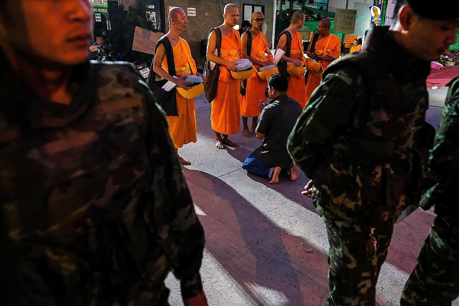 Monks receiving food from supporters. Amid a manhunt being carried out under the junta's wide-ranging powers, the temple has staged an international media campaign and alleged that its food supply has been curtailed.