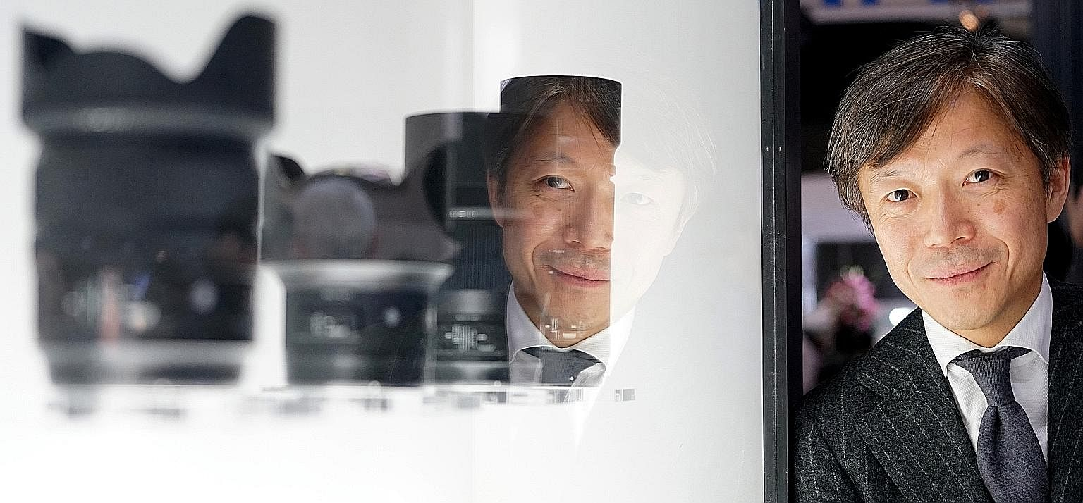 Mr Yamaki with the four new lenses Sigma launched at the CP+ Camera and Photo Imaging Show in Yokohama last week. He attributes the company's growth to its products' quality and unique features.