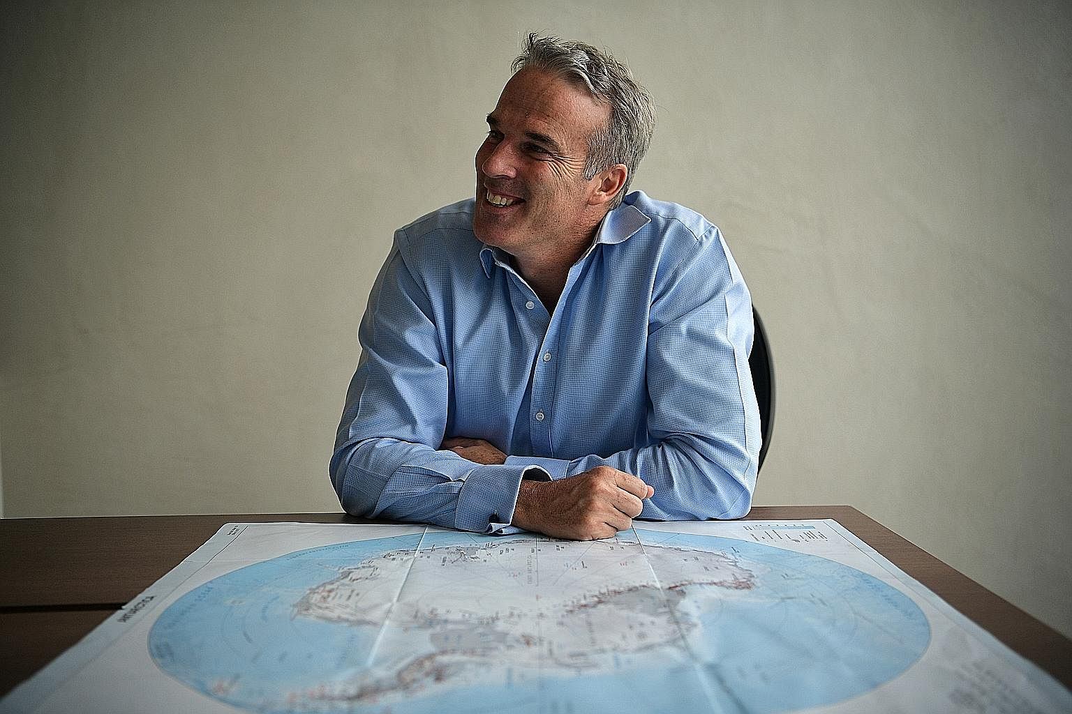 Mr Pugh with a map of Antarctica (above), where he is trying to create seven marine protected areas by 2020. He is often asked to give talks, such as this one about the oceans with children in the Maldives.