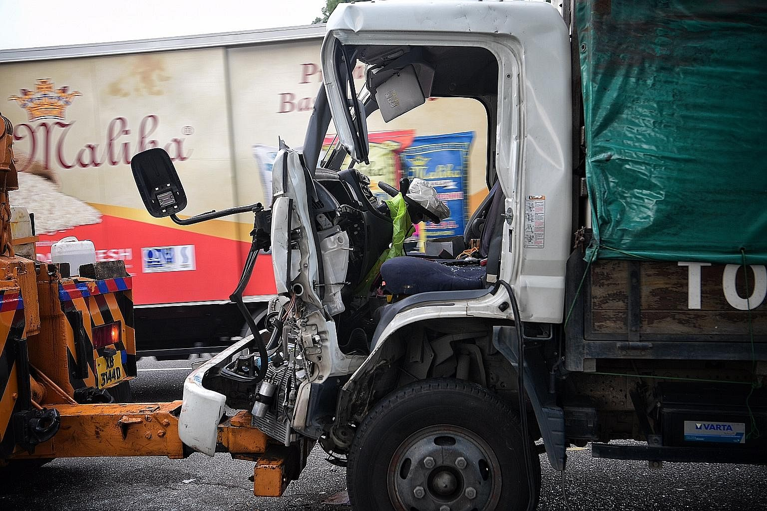 The force of the collision between a trailer and a lorry along AYE yesterday crushed the lorry's cabin, trapping the driver and two passengers. SCDF personnel used hydraulic power tools to extricate the three men from the wreckage. The accident cause