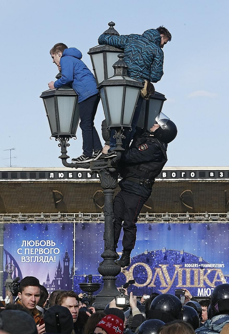 A riot policeman trying to get two protesters down from a lamp-post during a protest in Moscow on Sunday. Many young people were detained. A group that monitors police detentions said there were a lot of minors and students in police stations.