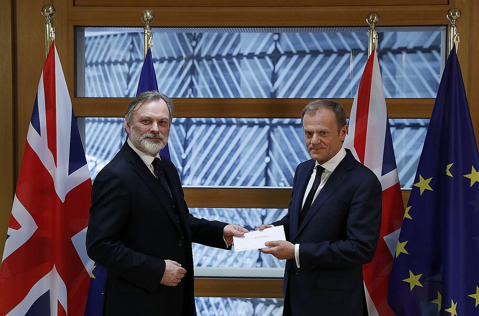 Britain's permanent representative to the European Union Tim Barrow (at left) delivering British Prime Minister Theresa May's Brexit letter to EU Council President Donald Tusk in Brussels yesterday.