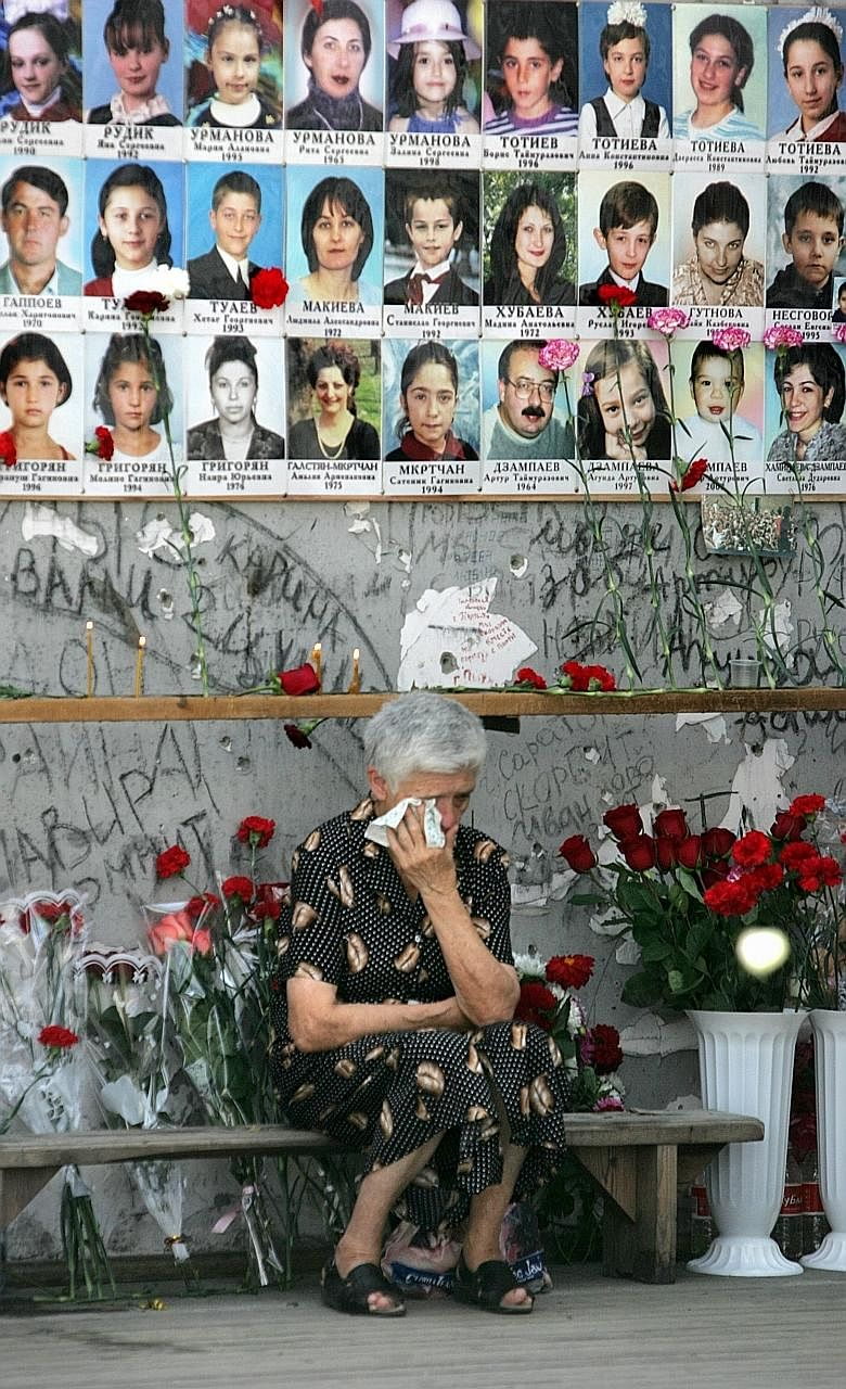 A 2009 file photo showing a woman at the Beslan school gymnasium mourning the victims of the 2004 siege by Chechen rebels, on the fifth anniversary of the incident. The school was stormed on Sept 1, 2004, by militants demanding the withdrawal of Russ