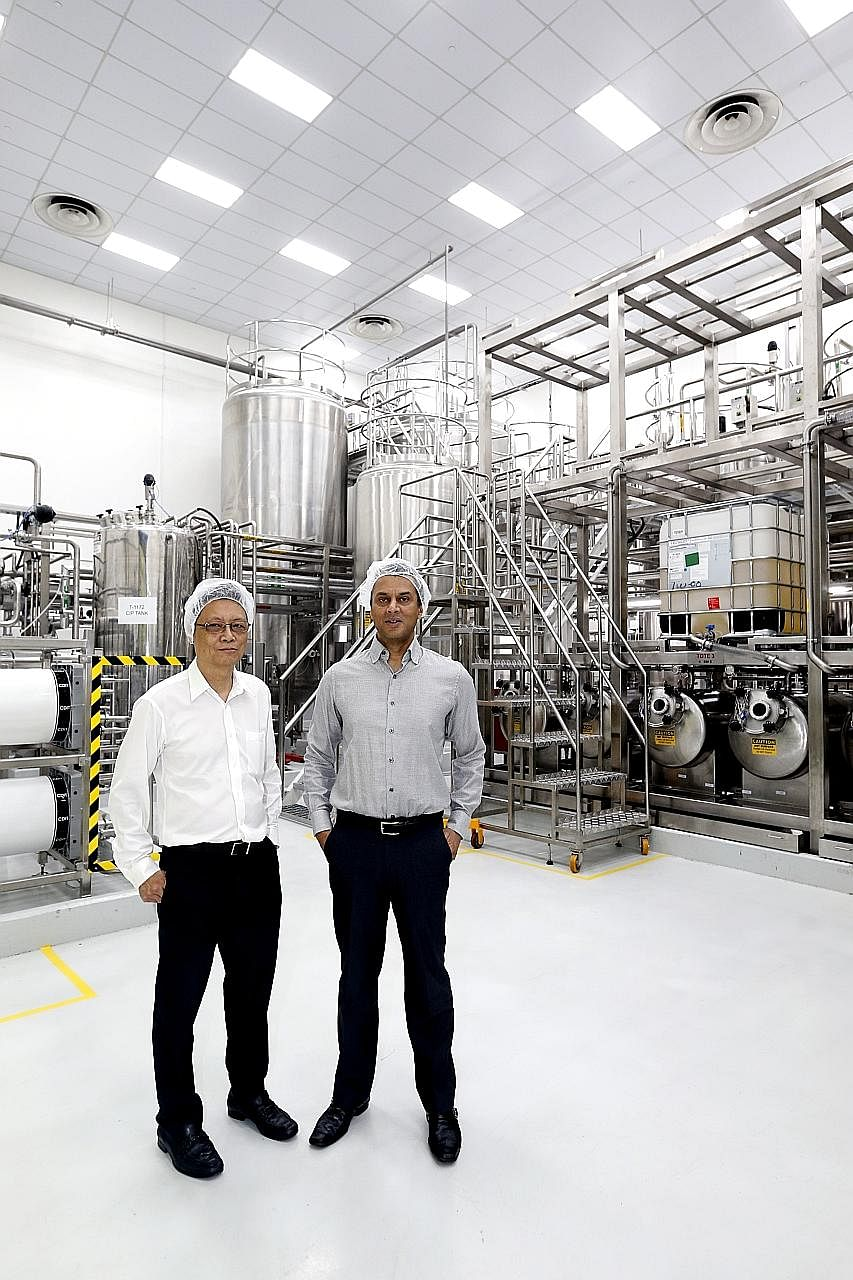 EEC managing director Lee Kwok Kuen and Kimberly-Clark's Asia-Pacific vice-president of product supply Peter D'Silva in front of the water purification system that EEC developed for Kimberly-Clark's new baby wipes production line.