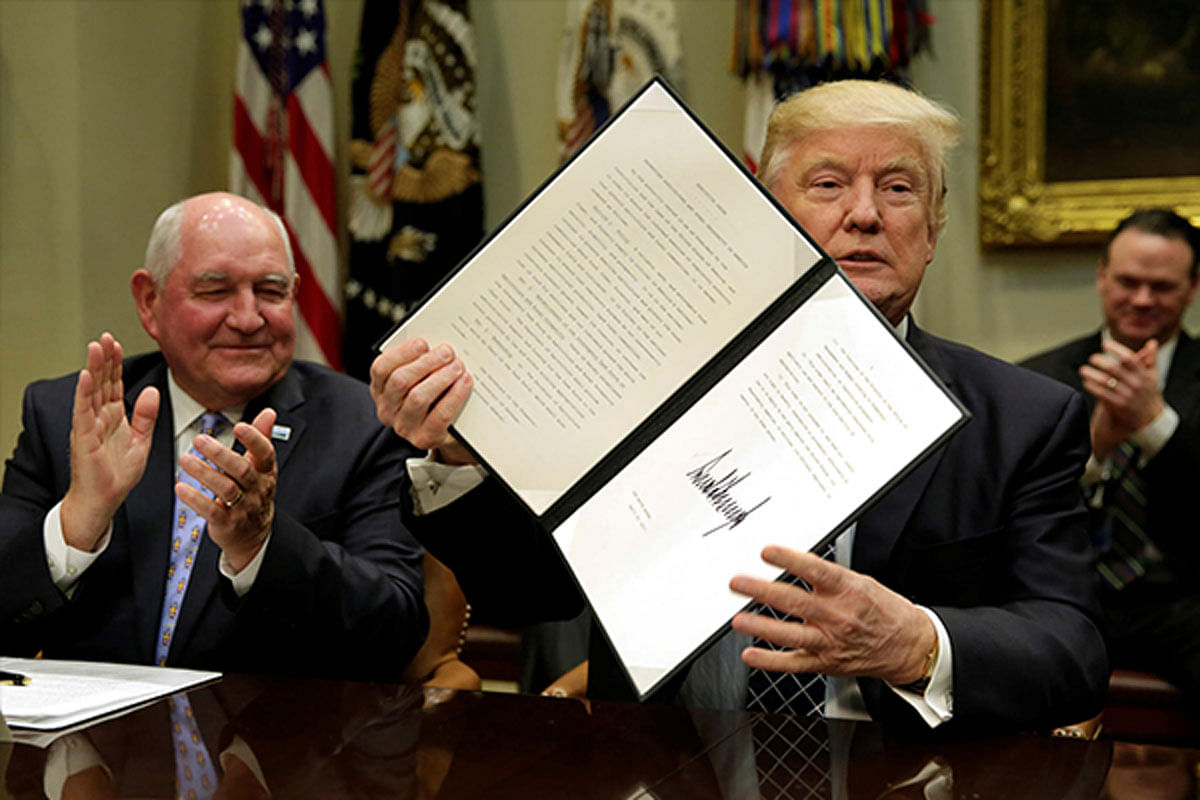 US President Donald Trump shows a signed executive order next to Secretary of Agriculture Sonny Perdue during a roundtable discussion with farmers at the White House.