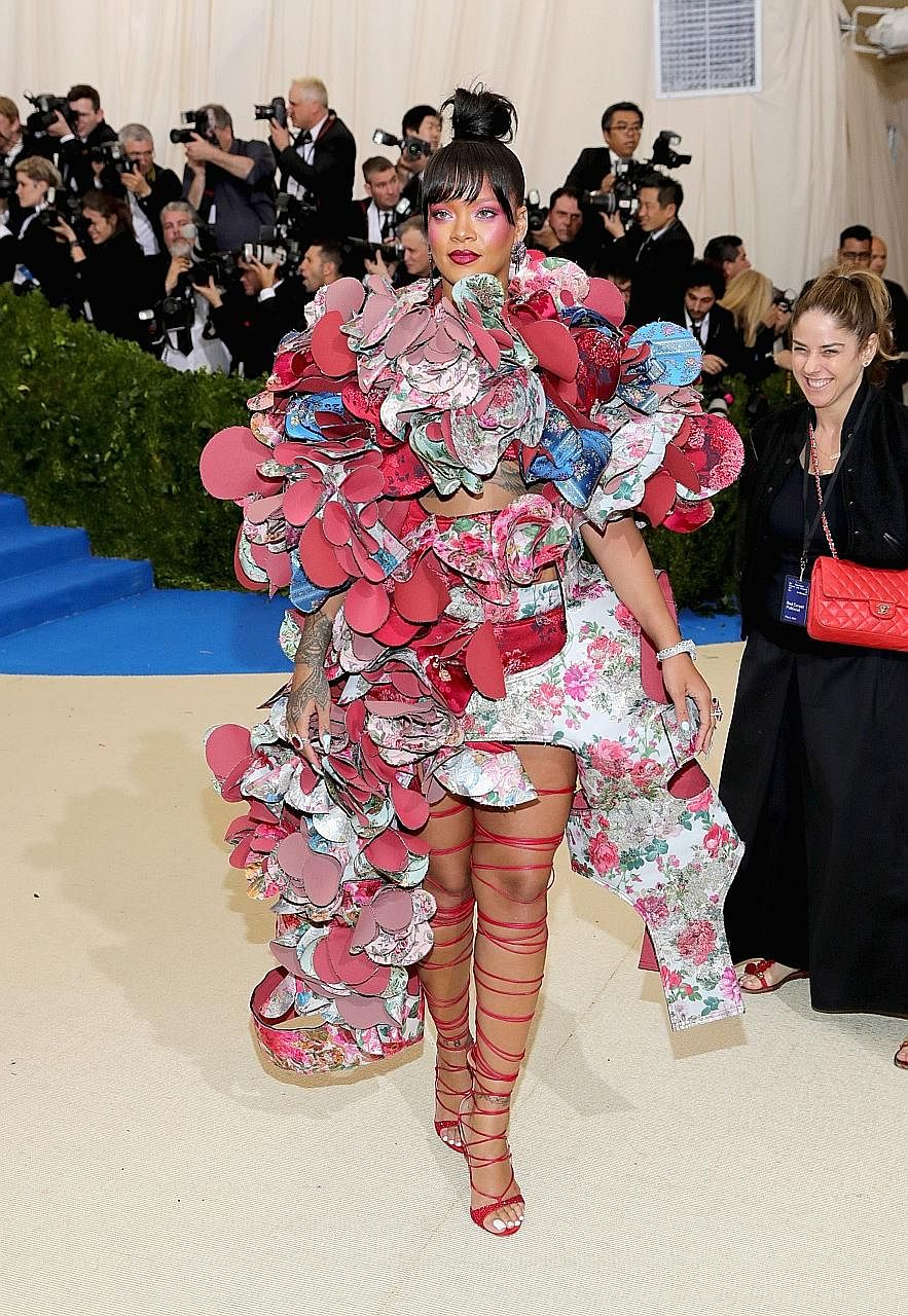 Singer Rihanna in a kaleidoscopic Comme des Garcons dress with swirling layers of floral flounces.