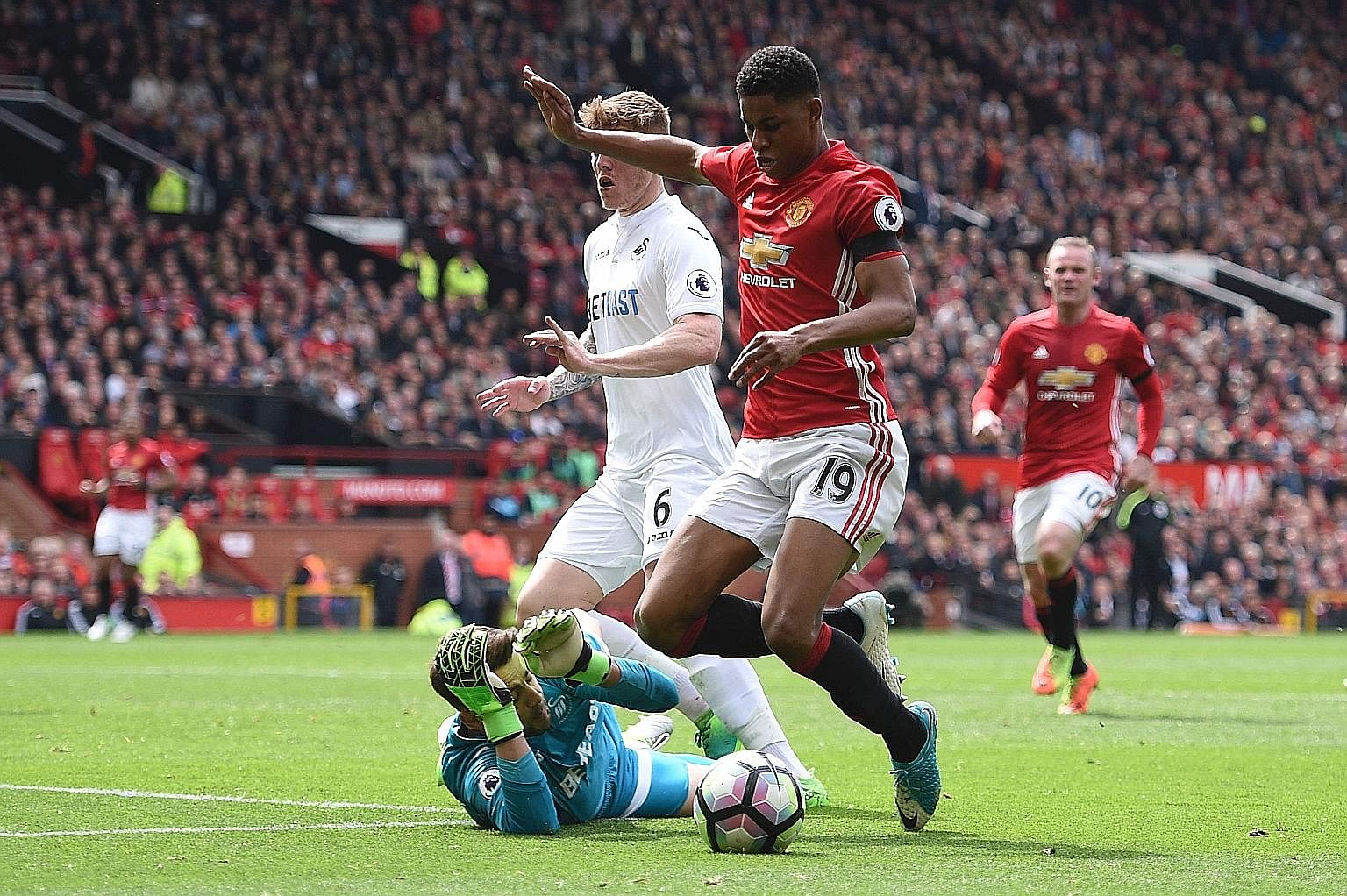 Manchester United's English striker Marcus Rashford goes down as Swansea goalkeeper Lukasz Fabianski pulls his arms away. His dive earned his side a penalty in the English Premier League clash.