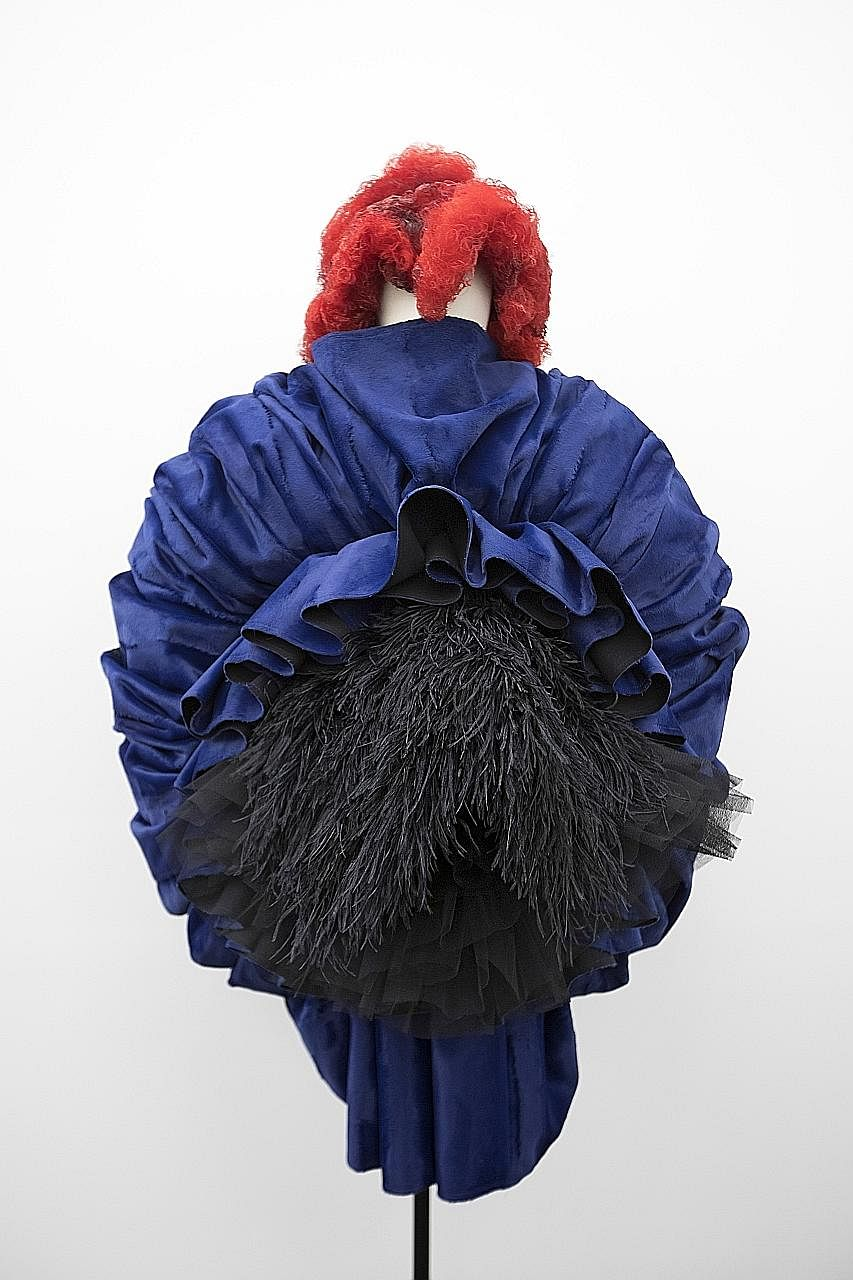 Outfits (top and left) by Rei Kawakubo (above) at the exhibition held at New York's Metropolitan Museum of Art.