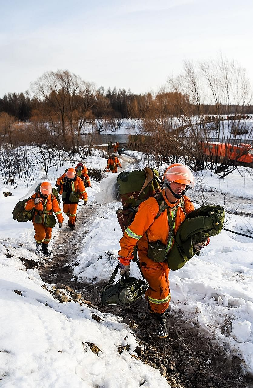 Chinese firefighters leaving the Bilahe Beidahe Forest. A sudden heavy snowfall overnight on Saturday covered the forest in Inner Mongolia with an 18cm blanket of snow, helping to douse a massive forest fire in the mountainous region near the Russian