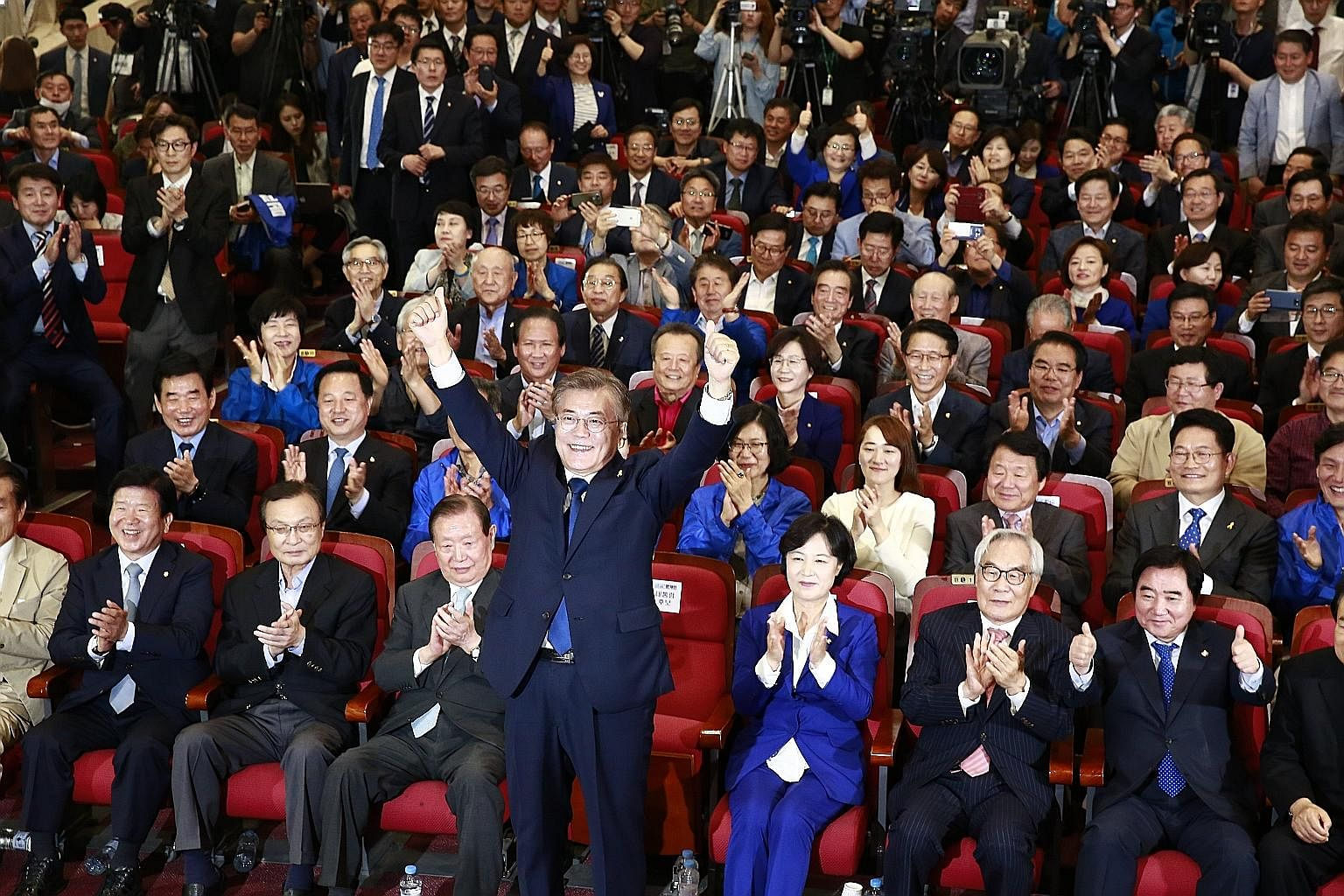 Mr Moon Jae In of the Democratic Party celebrating with supporters at the National Assembly in Seoul, after exit polls showed he would be South Korea's new president. People watching a live broadcast of election coverage in Seoul's Gwanghwamun Square