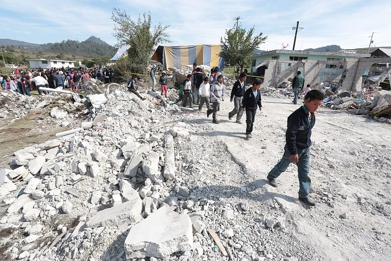 Villagers standing amid the rubble after the explosion