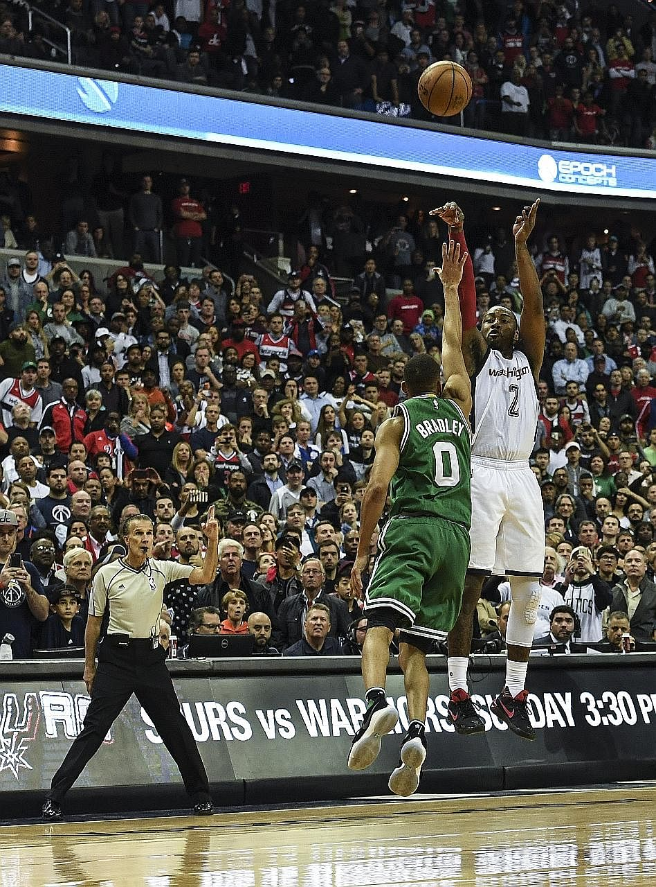 Wizards guard John Wall shoots the game-winning three-pointer over Celtics guard Avery Bradley with seconds to spare. The Eastern Conference series goes to a Game Seven at Boston.