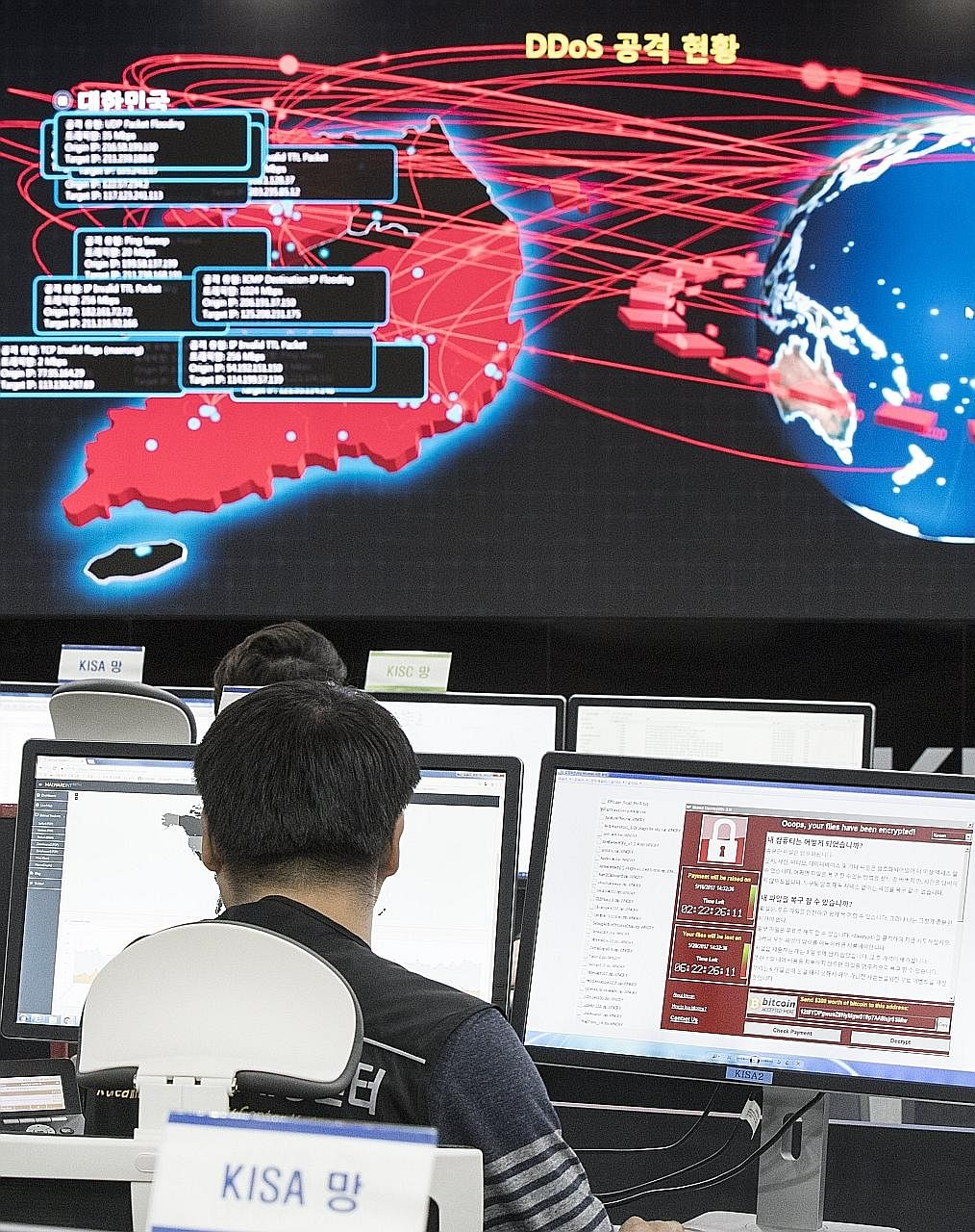 Employees watching an electronic board to monitor possible cyber attacks at the Korea Internet and Security Agency in Seoul yesterday.