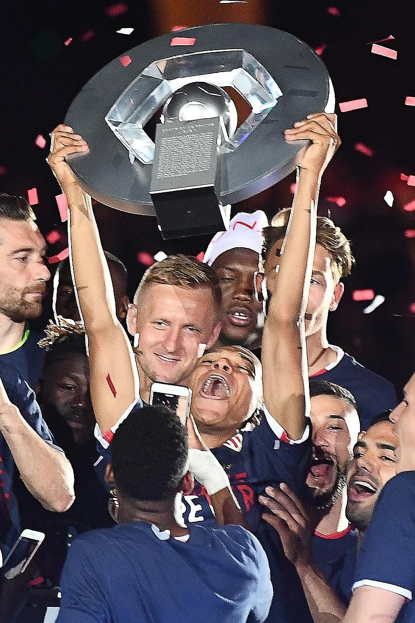 Monaco forward Kylian Mbappe hoisting the Ligue 1 trophy after they beat Saint Etienne 2-0 on Wednesday. He opened the scoring and substitute forward Valere Germain sealed the win for the side's first French league title in 17 years.