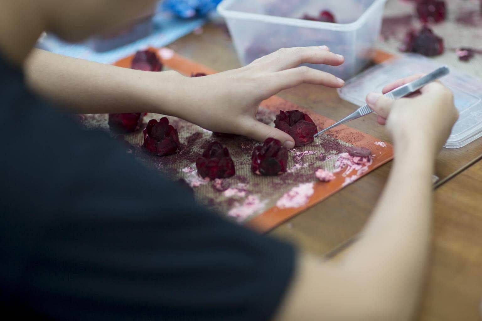 A chef prepares a 'beetroot-rose' dessert inside the research and  development kitchen at Gaggan restaurant in Bangkok, Thailand, on May 5,  2017.