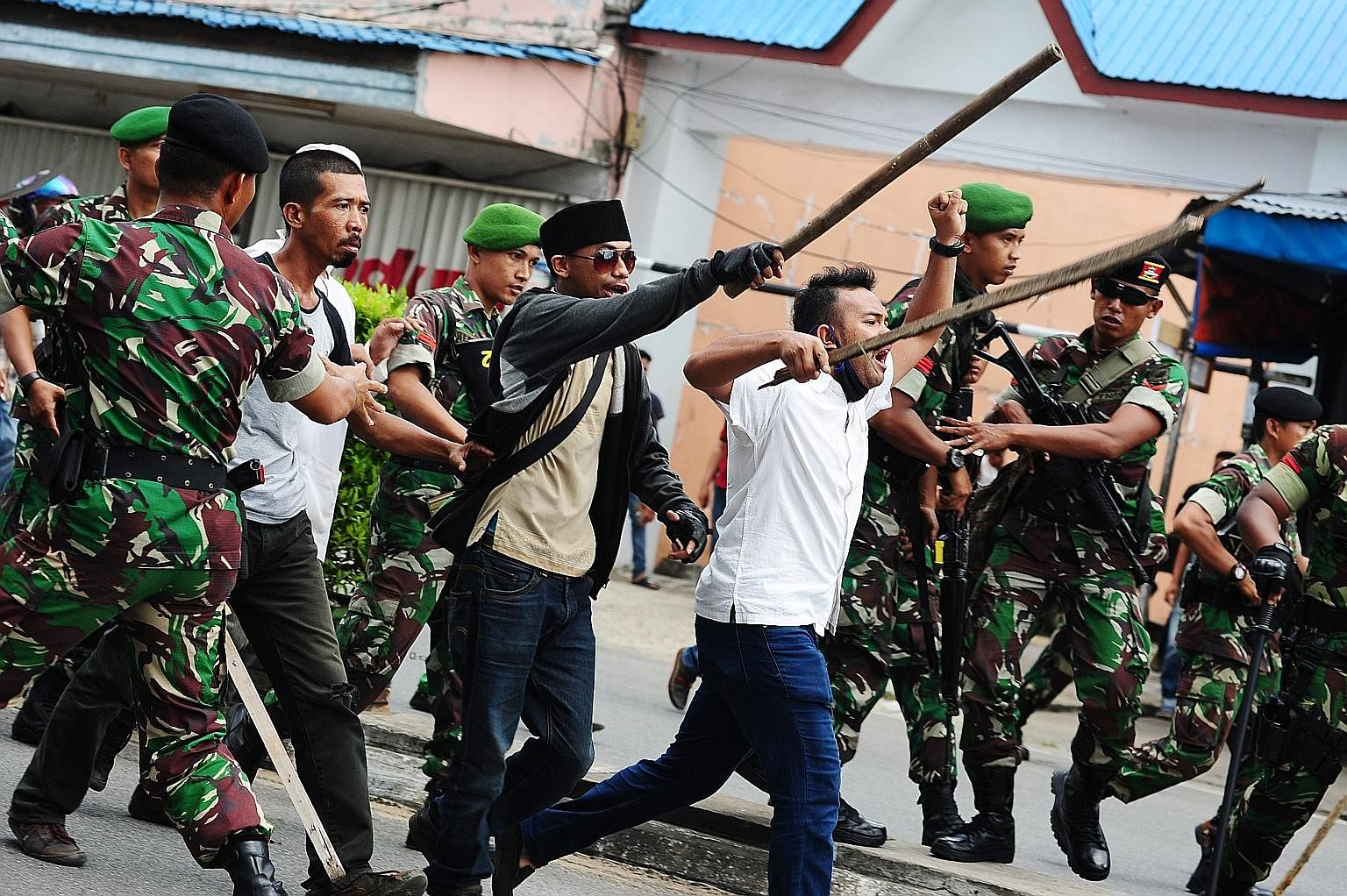 Indonesian hardline Muslim activists being restrained by military personnel as they shouted slogans during a local tribal festival in Pontianak, West Kalimantan province, on May 20. The divisive gubernatorial Jakarta election has brought up the quest
