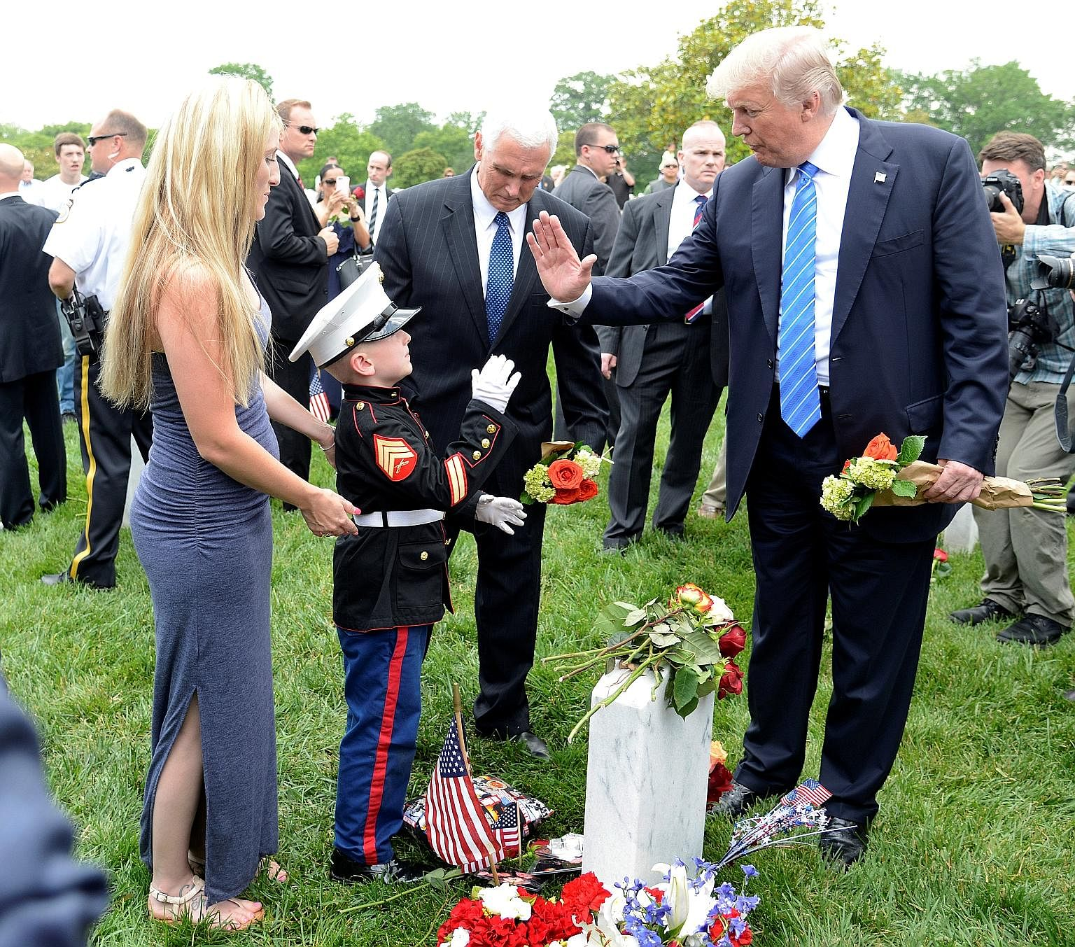 Mr Donald Trump exchanging high fives with the son of a US marine who was killed in training, as the boy's mother looks on, at Arlington National Cemetery in Virginia, which the US President visited on Monday to mark Memorial Day.