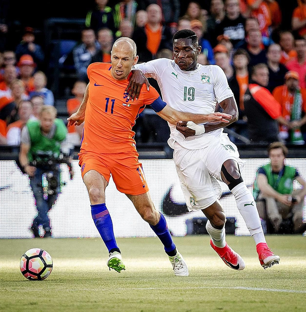 Netherlands captain Arjen Robben shielding the ball from Ivory Coast defender Simon Deli during a friendly in Rotterdam. The hosts won 5-0, with Robben scoring their second last Sunday.