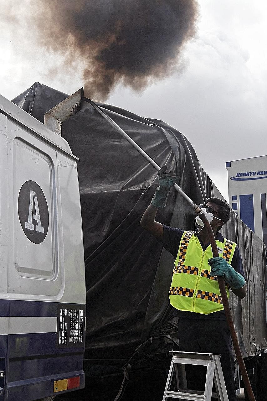 Mr Ganesan Naransamy, 27, an auxiliary police officer sticking a probe into the exhaust pipe of a lorry yesterday. The probe is connected to a Hartridge Smoke Meter, which measures the opacity of smoke emitted.