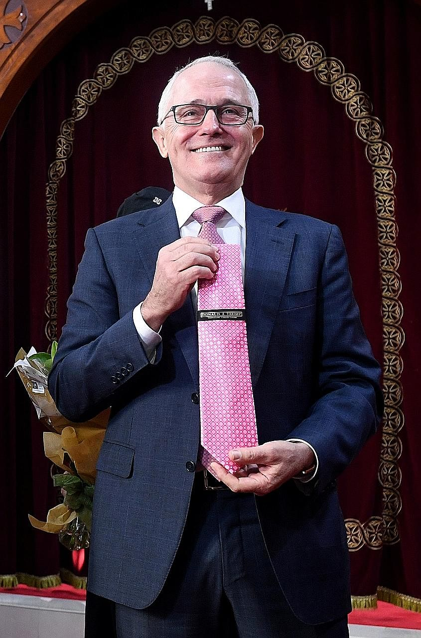 Australian Prime Minister Malcolm Turnbull, who has had frosty relations with United States President Donald Trump at times, received a pink Trump-branded tie yesterday as a gift during a visit to a Coptic Orthodox church. He appeared bemused after r