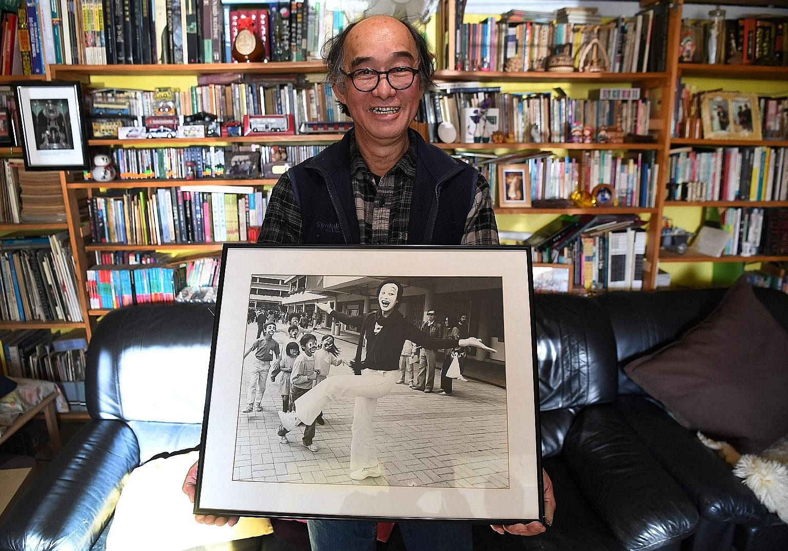 Mr Philip Fok with a photo of himself in his younger days as a mime artist in Hong Kong. He emigrated to Sydney in 1992. Hong Kong residents holding up placards with words depicting their feelings about the city as the 20th anniversary of its handove