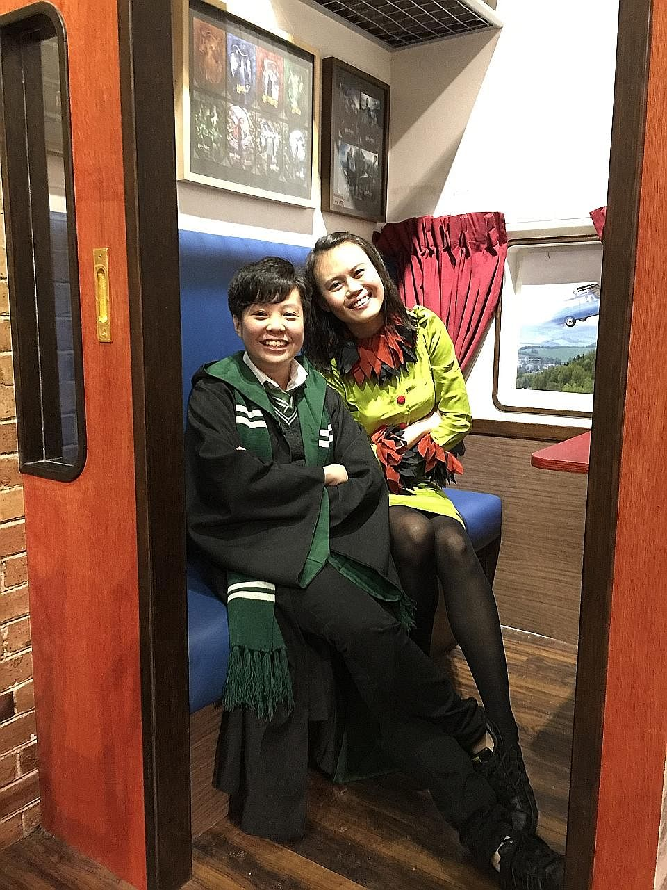 Ms Chin Xuan (far left), in a Slytherin school uniform, and Ms Jo Chua, wearing a Rita Skeeter outfit she made herself. The ardent Harry Potter fans are sitting in a Hogwarts Express train carriage at the Singapore Philatelic Museum's Harry Potter exhibit