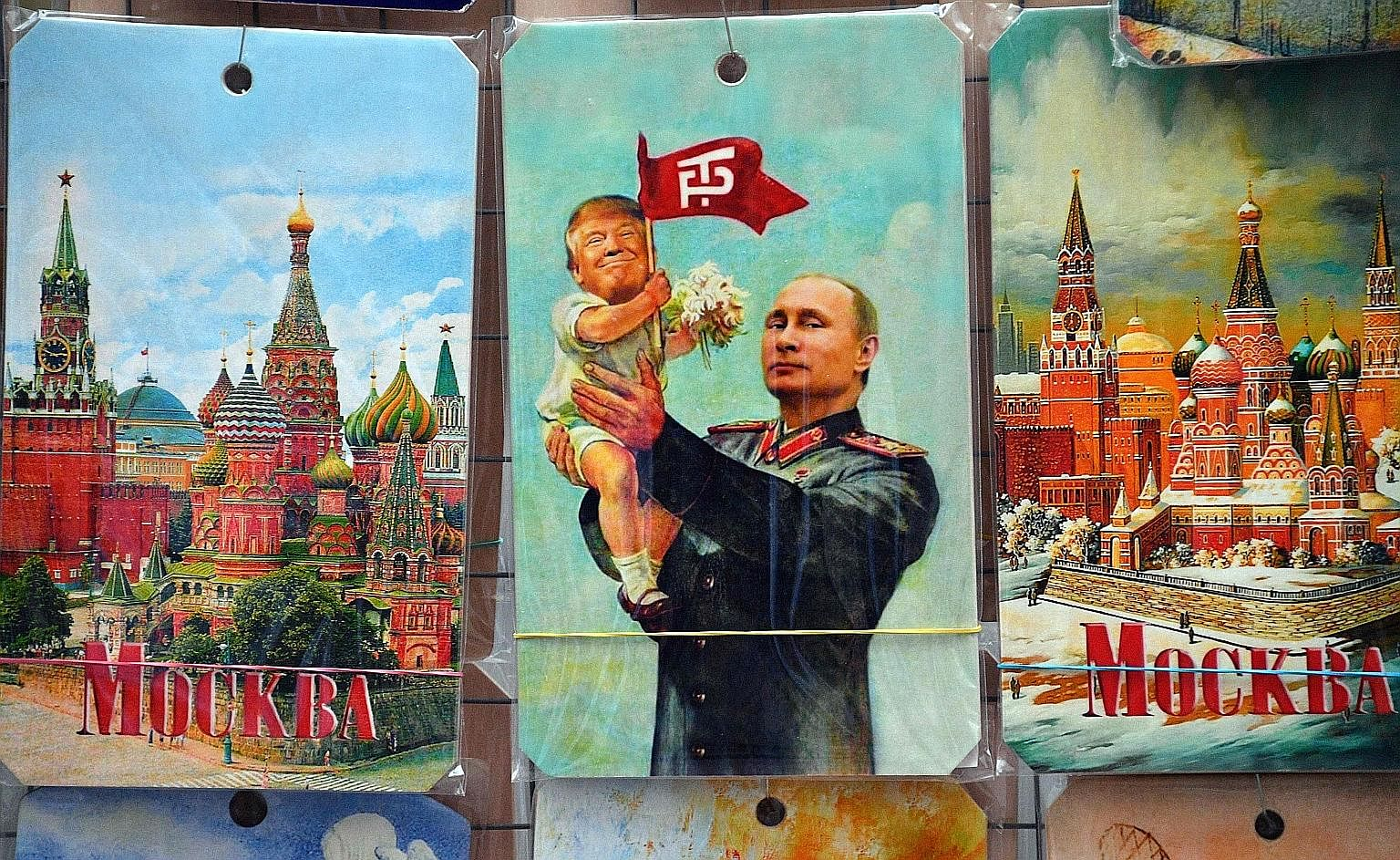 A drawing on sale in a souvenir shop in Moscow depicting Russian President Vladimir Putin holding a baby with the face of US President Donald Trump, based on an old propaganda poster showing former Soviet leader Joseph Stalin holding a baby. The firs