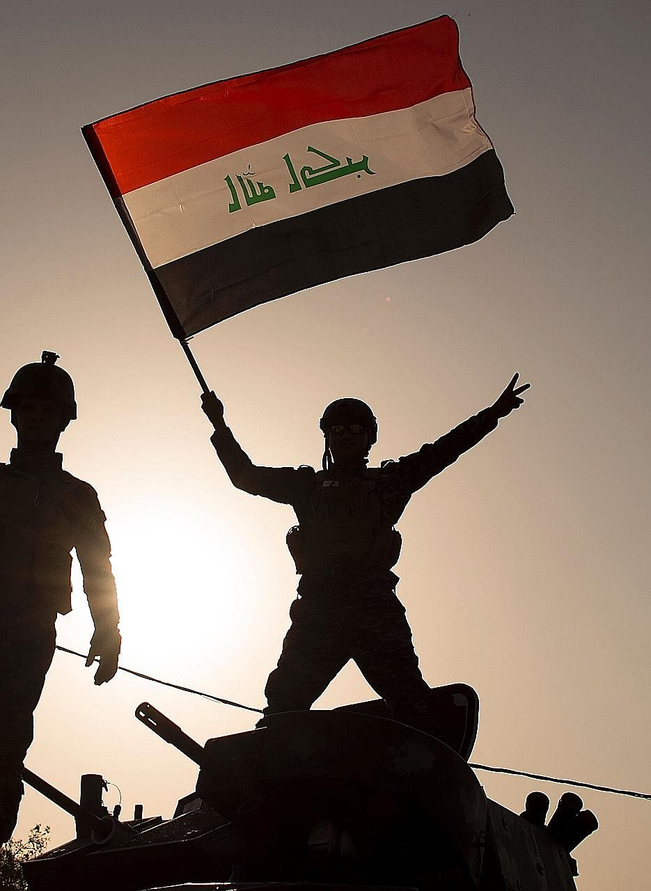 An Iraqi federal police officer waving the national flag as he celebrates in the Old City of Mosul on Sunday after its liberation.