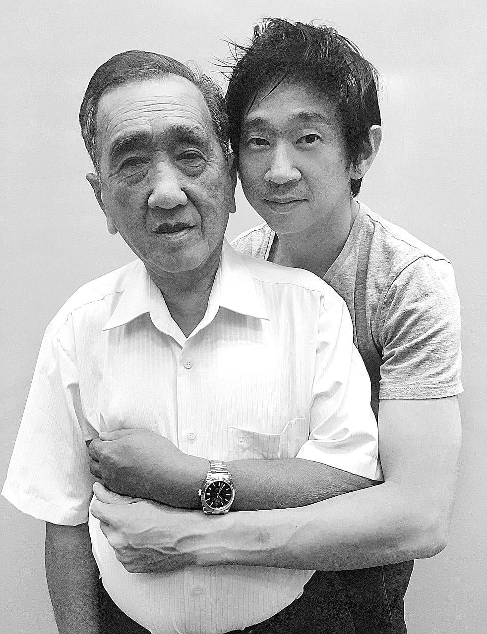 Photographer John Clang with his father Ang Ching Seong, who is wearing his son's Rolex Milgauss watch (above).
