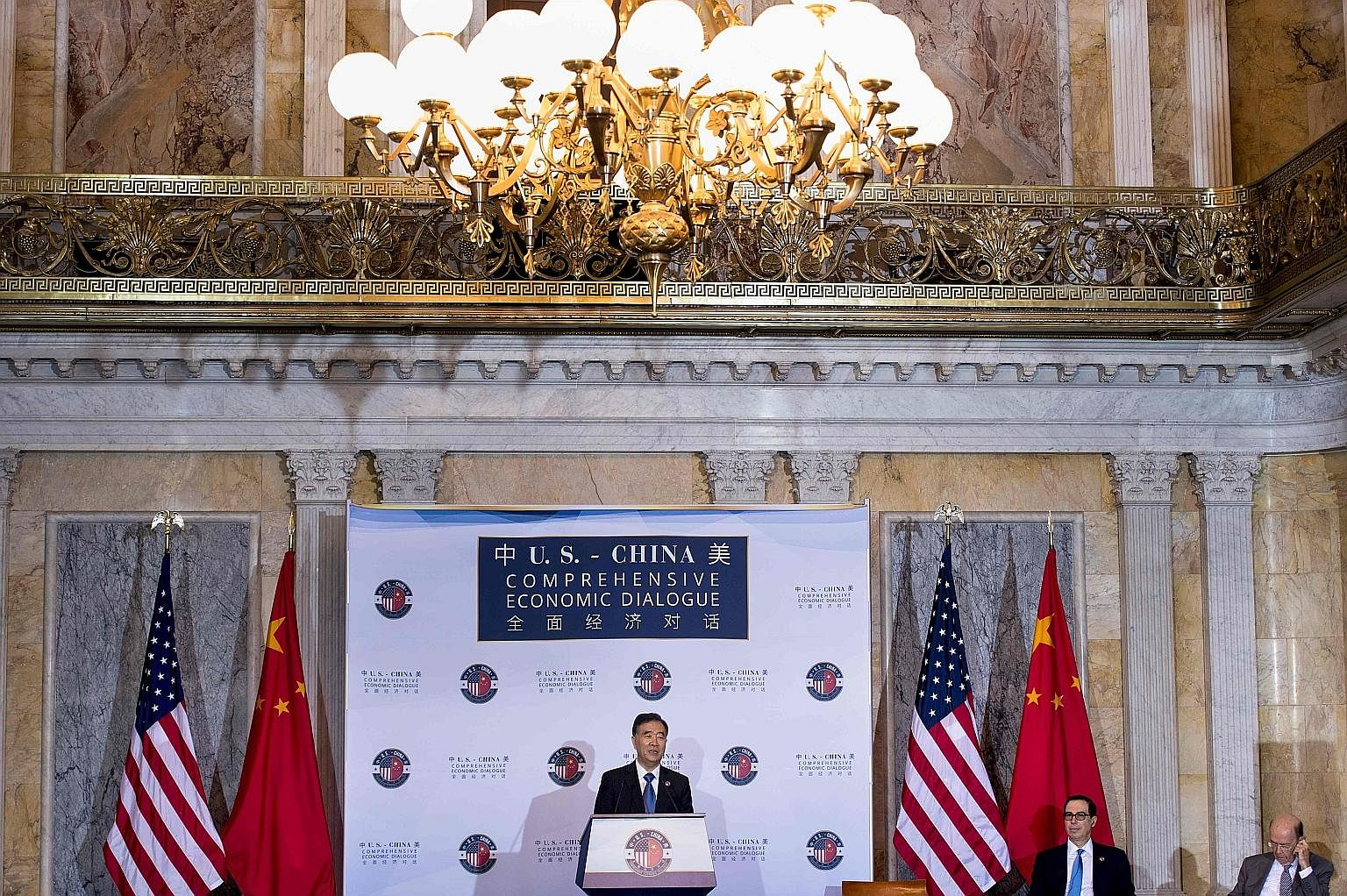 China's Vice-Premier Wang Yang speaking at the economic dialogue on Wednesday in Washington, as US Treasury Secretary Steven Mnuchin and Commerce Secretary Wilbur Ross (far right) listened.