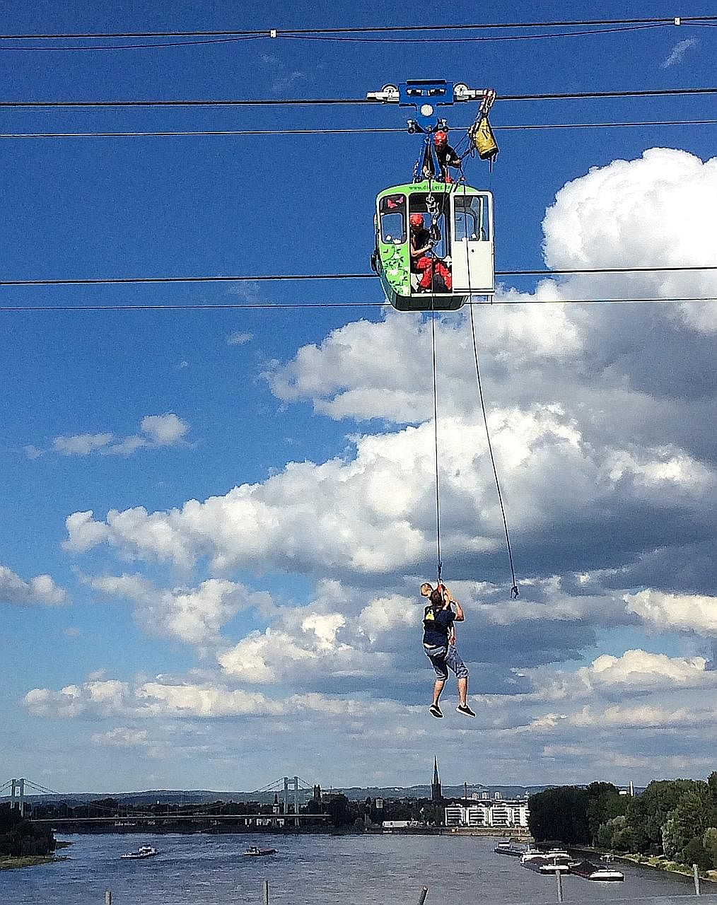 A man and his child being rescued from a cable car over the Rhine River in Cologne, Germany, on Sunday. A cable car had crashed into a support pillar, stranding dozens of passengers in midair.