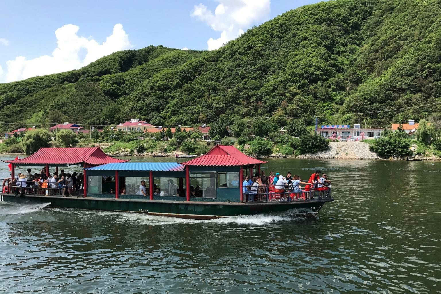 Chinese tourists are seen on a boat taking them from the Chinese side of the Yalu River for sightseeing close to the shores of North Korea