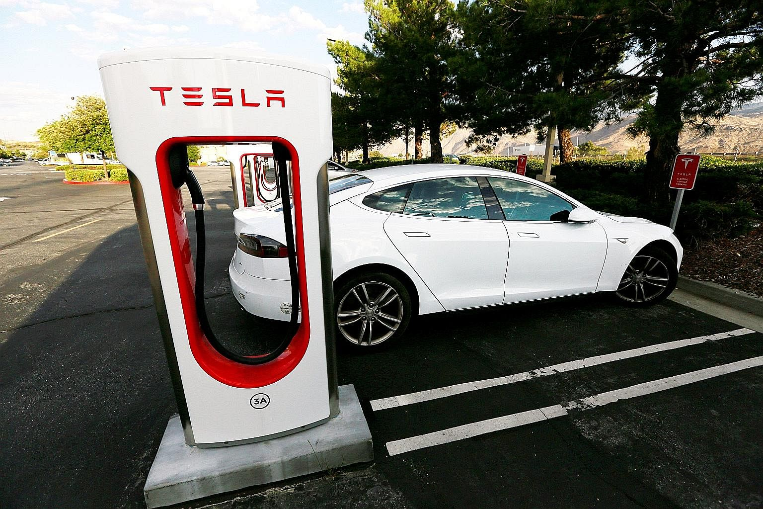 A Tesla Model S at a Tesla Supercharger station in Cabazon, California. The fleet of electric vehicles in use worldwide is on track to displace about 100,000 barrels a day of road transport fuel this year - most of it petrol.