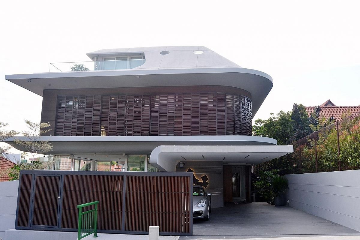The rounded grey facade of this house with two skylights punched into its roof makes it look as if a spaceship has landed on top of a hill in siglap