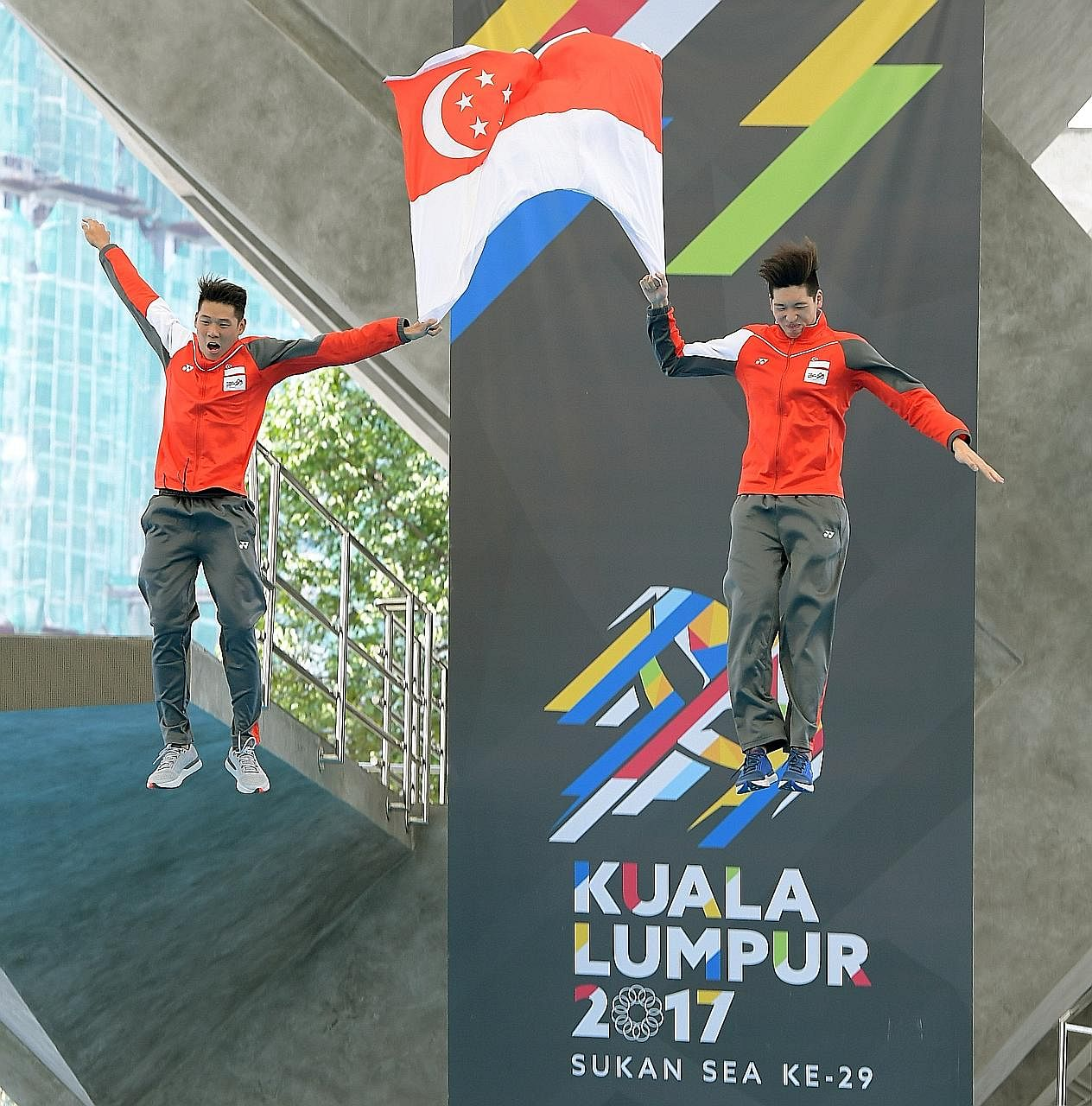 SEA Games water polo debutants Chow Jing Lun (left) and Yu Junjie jumping from the diving platform while holding the Singapore flag after winning the gold at Kuala Lumpur's National Aquatic Centre. It is a tradition for players making their Games bow