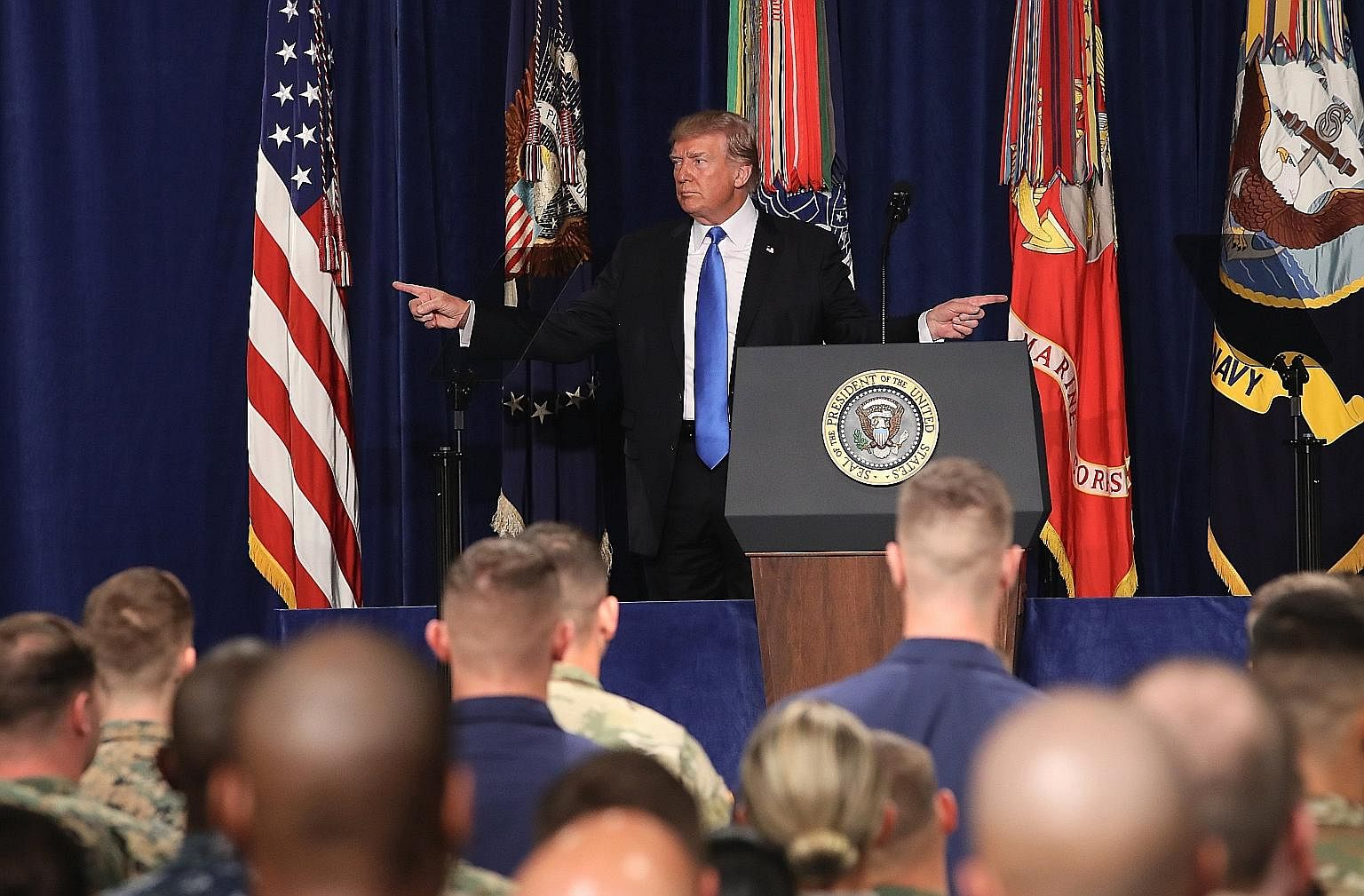 US President Donald Trump before delivering remarks on his country's military involvement in Afghanistan at the Fort Myer base, in Virginia, on Monday. The US is expected to send about 4,000 troops to join the roughly 8,400 in Afghanistan to be