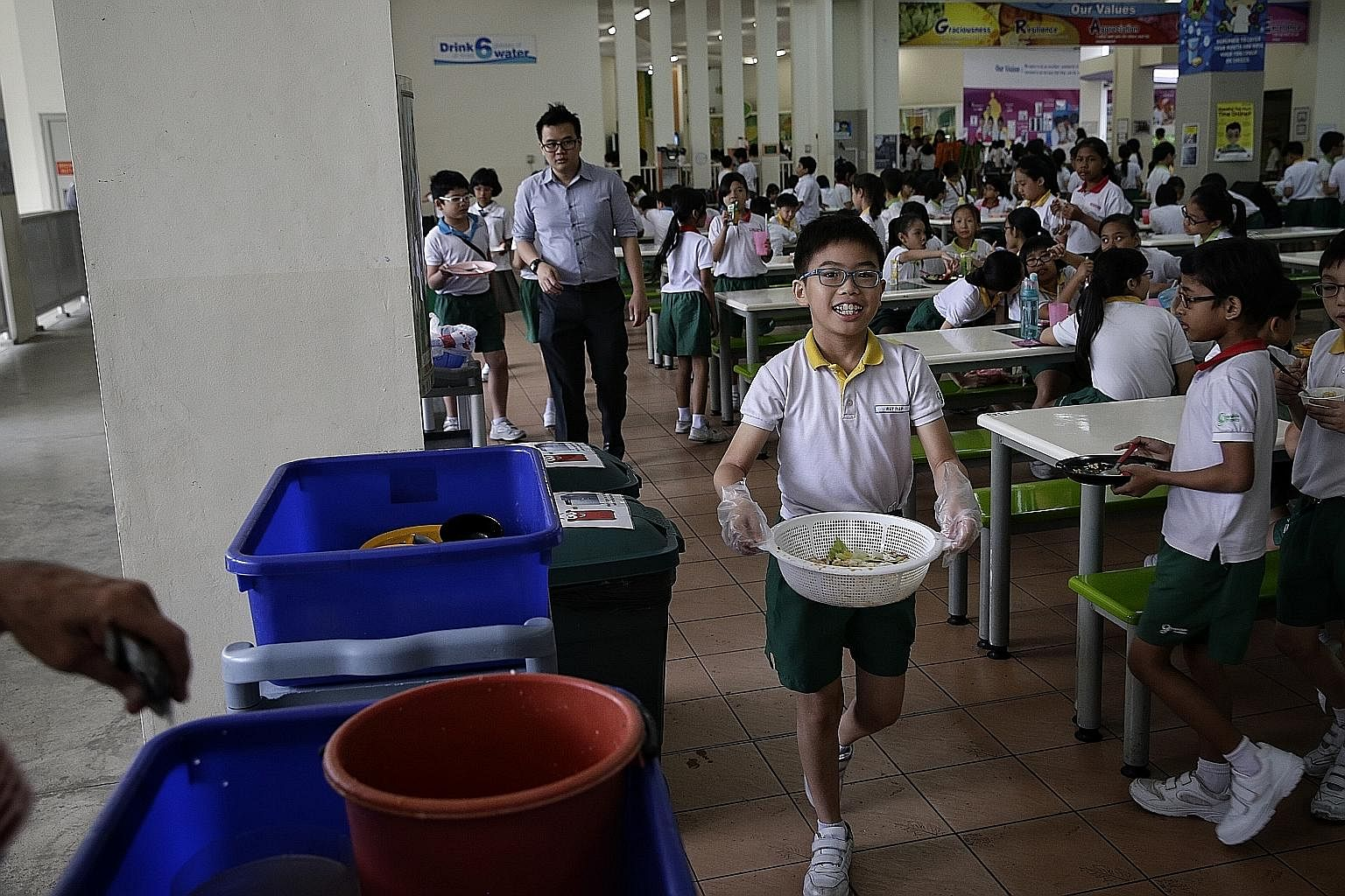 Eleven-year-old Ray Yap, a Primary 5 pupil of Greendale Primary School and a member of its environmental science club, carrying segregated food waste to a food-waste digester on Tuesday. The school started a food-waste reduction programme last month.