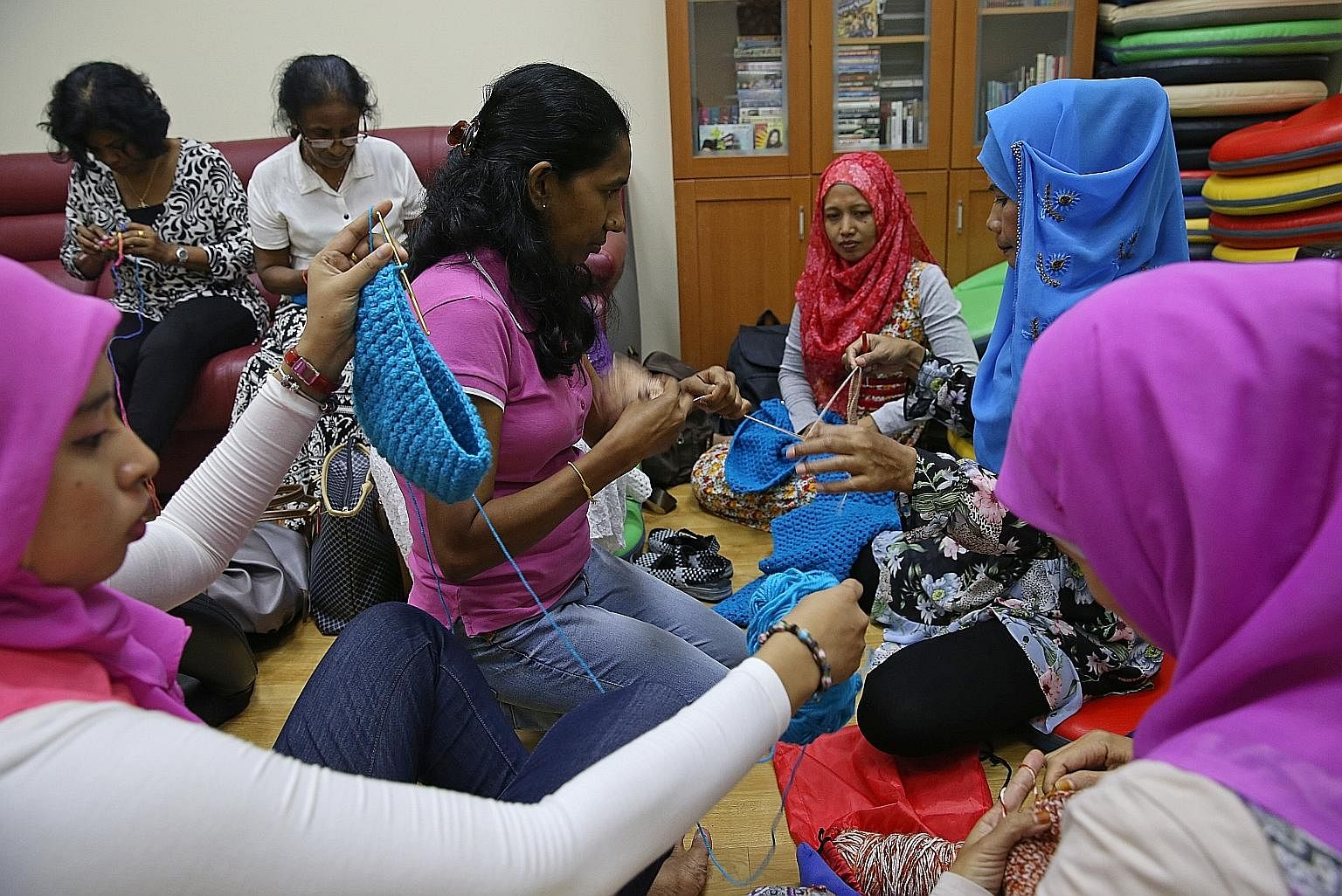 Indonesians Tri Susanty (far left, wearing a purple tudung), 29, Rina Waty (third from right, in a red tudung), 41, and Sunarmi (in a blue tudung), 42, sharing crochet tips with Sri Lankan Chamila, 42, during class. Besides being able to make shawls to pr