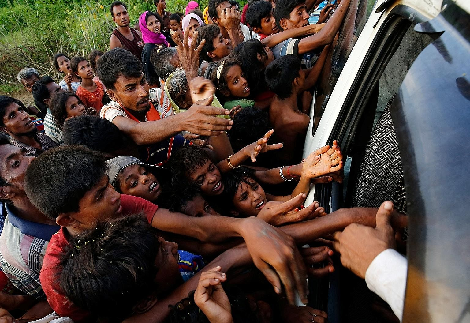 Rohingya refugees reaching for food being distributed near Balukhali in Cox's Bazar, Bangladesh, on Monday. The weight of the majority in mostly Buddhist Myanmar is against the Muslim Rohingya, says the writer, and the popular call is for the army to