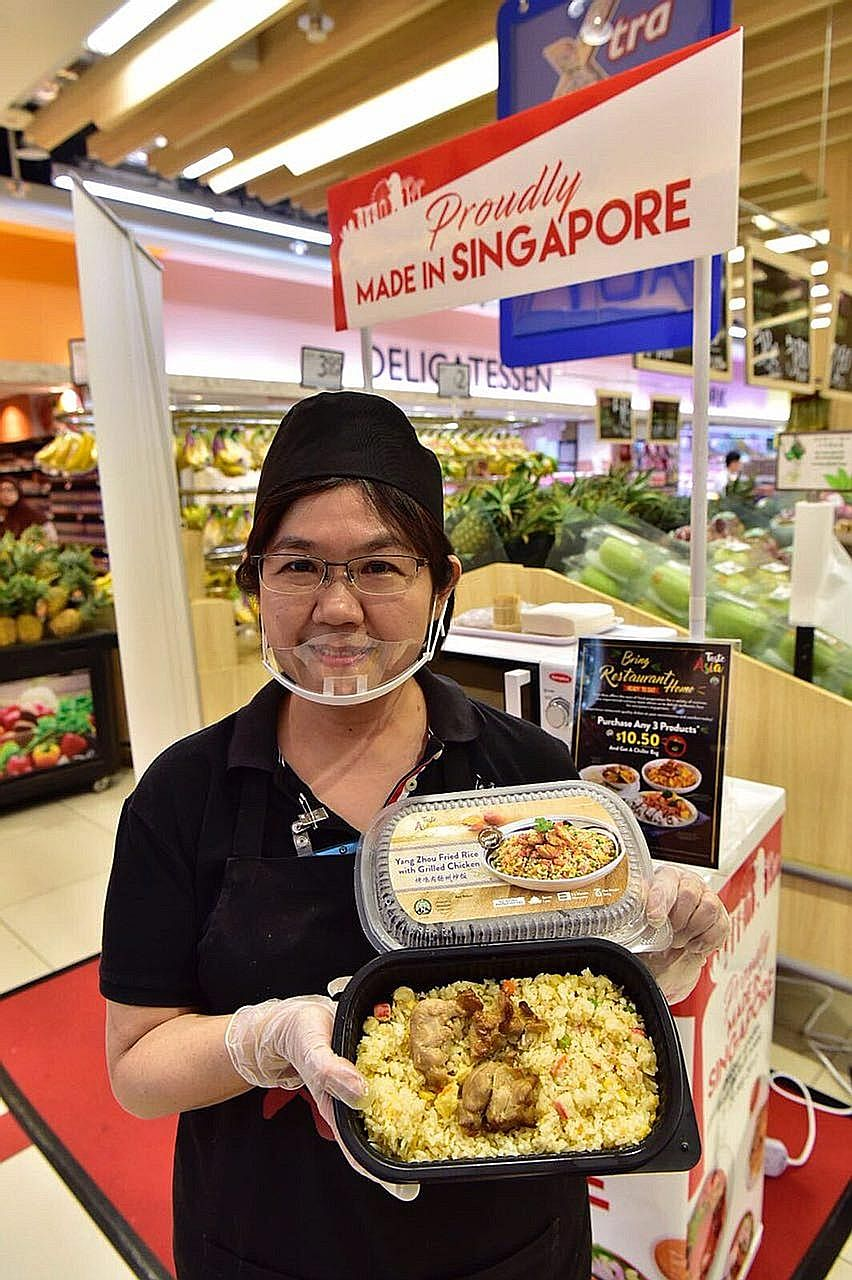 Sales promoter Daphne Lee, 52, with a ready-to-eat meal of Yang Zhou fried rice with grilled chicken, one of the locally made products in FairPrice's Made in Singapore Fair.