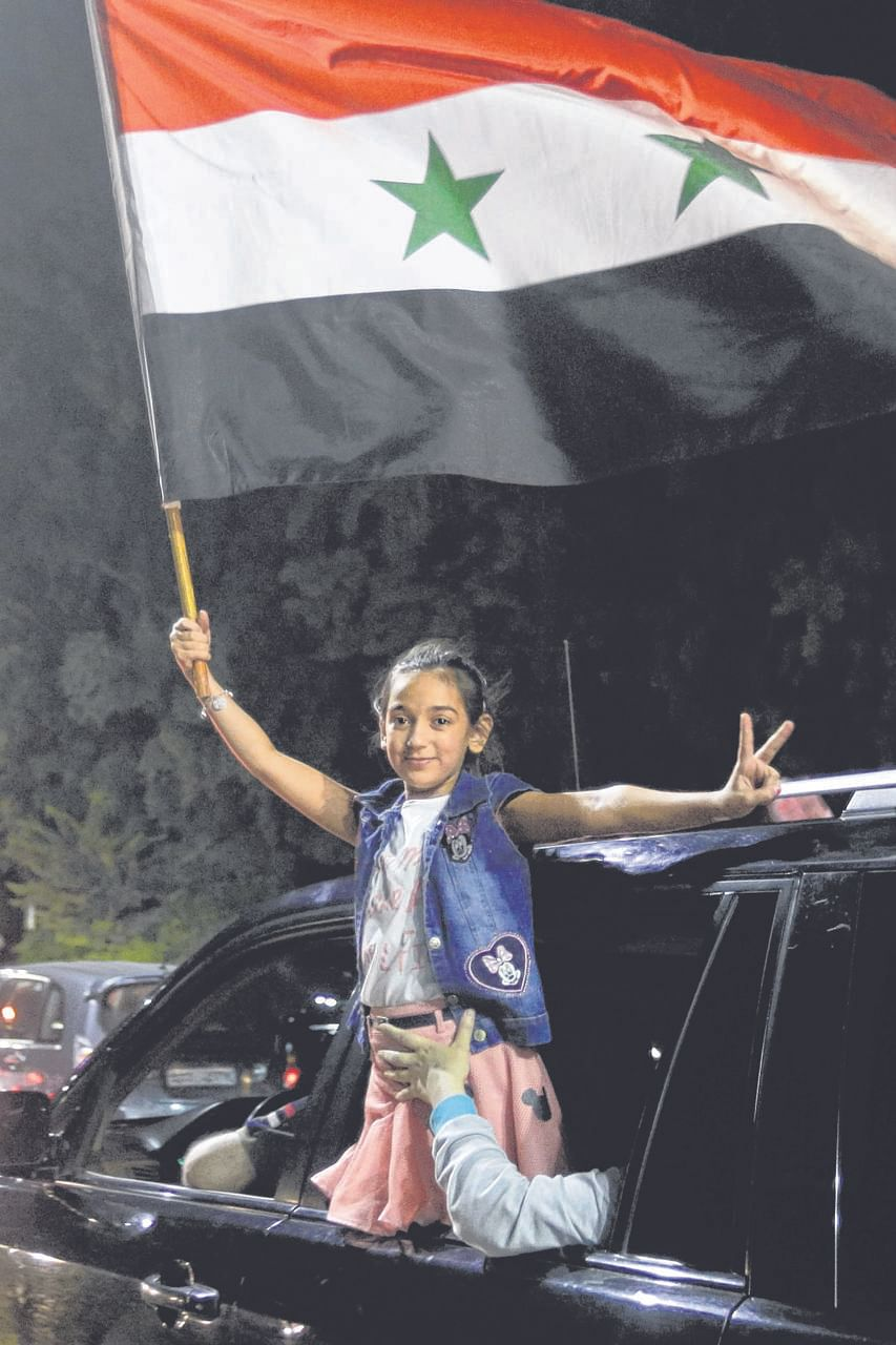 A young Syrian fan celebrates after the national side scored an injury-time equaliser against Iran during a World Cup qualifier.