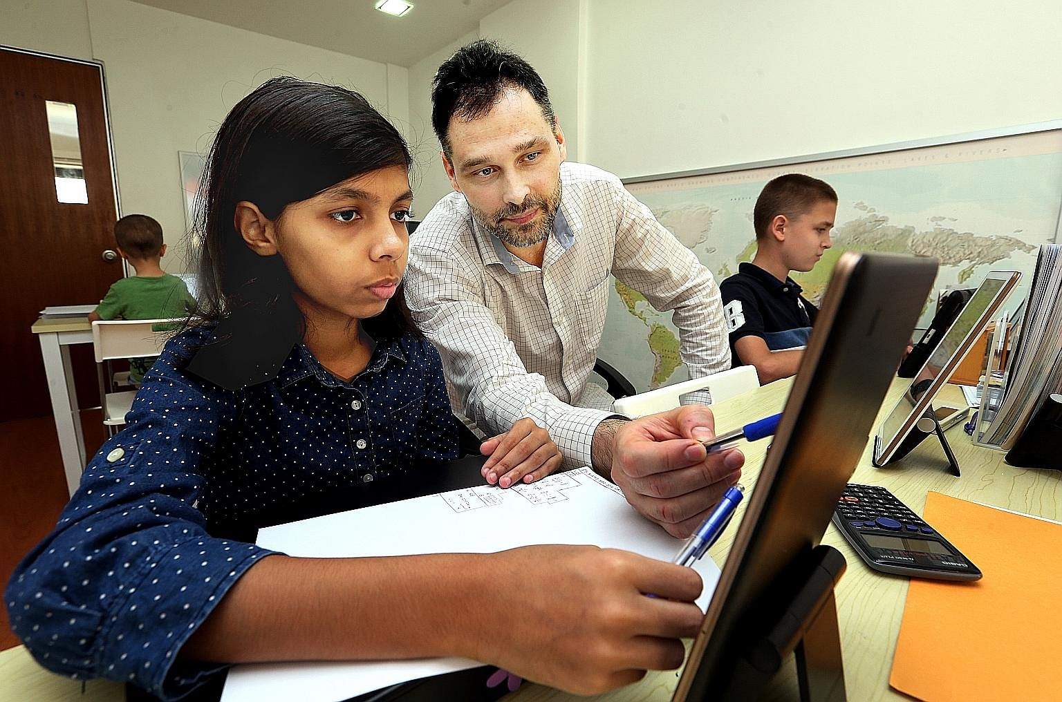 Dr Alexander Kuznetsov with student Shaistha Ahmed, 12. Armed with a PhD in maths and a master's in psychology, he has rapidly expanded his tuition centre in Yishun. His vision is to set up an international school here. Dr Kuznetsov wants his sons (f