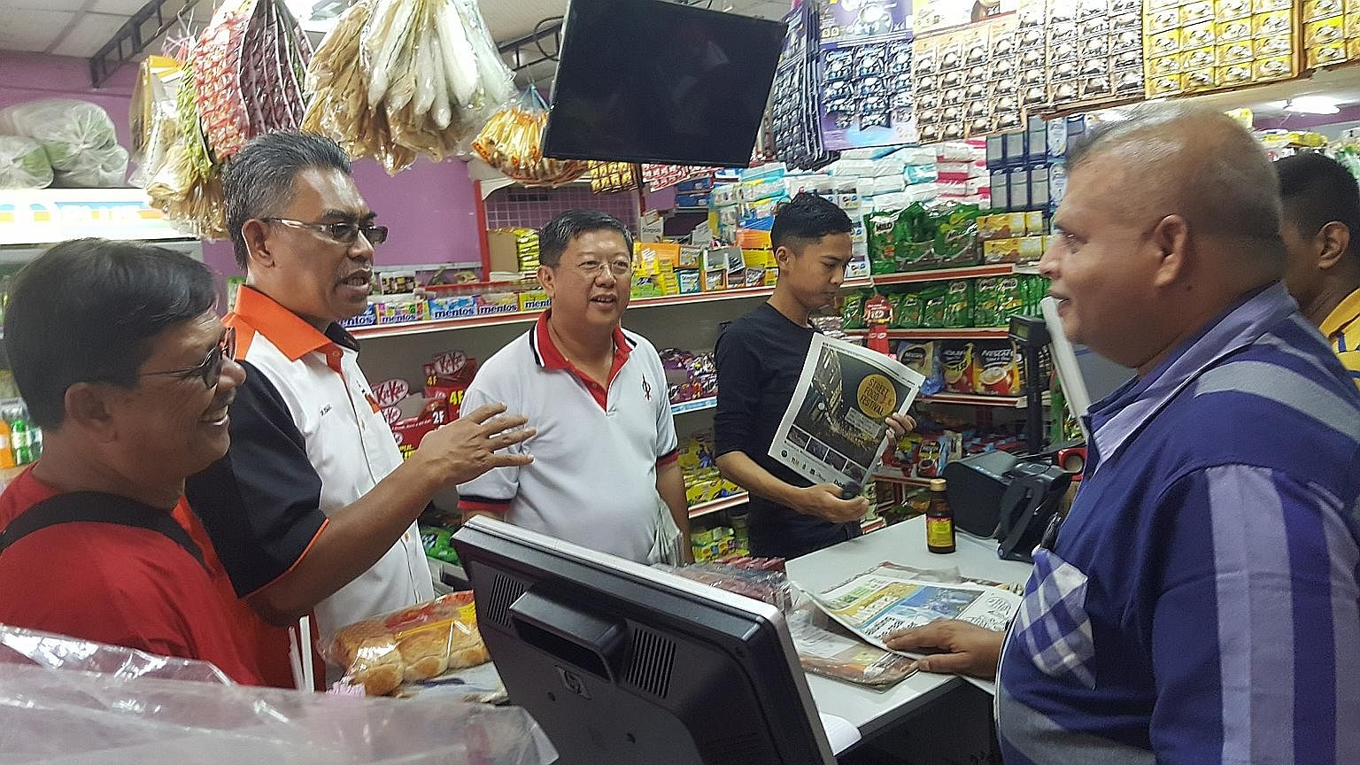 Kedah Amanah chief Ismail Salleh speaking with residents as he and DAP assemblyman Tan Kok Yew work the ground in Ayer Hitam in Kedah. Their Pakatan Harapan alliance is going all out to break the ruling coalition's grip in state strongholds, hoping t