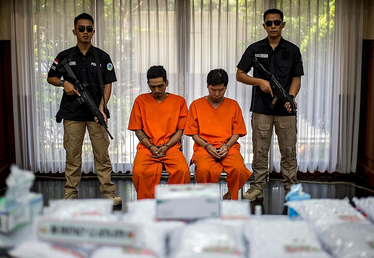 Indonesian police with two suspects after a raid on a warehouse on the outskirts of Jakarta on July 21, where the authorities seized Ecstasy pills. There has been a rise in the trafficking of Ecstasy, heroin, and methamphetamine into Indonesia, and l